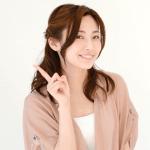 人差し指を立てる笑顔の女性