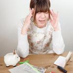 通帳と貯金箱と残金を前に悩む女性