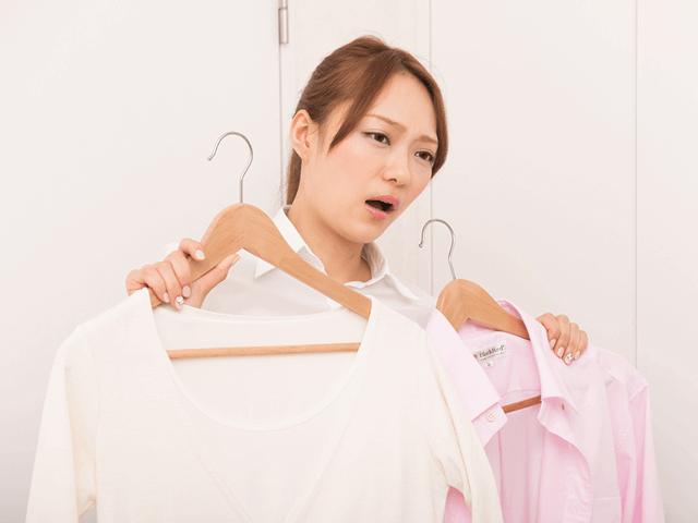 どの服を着るか悩む女性