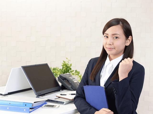 ノートPCの前でガッツポーズをするスーツの女性、オフィス