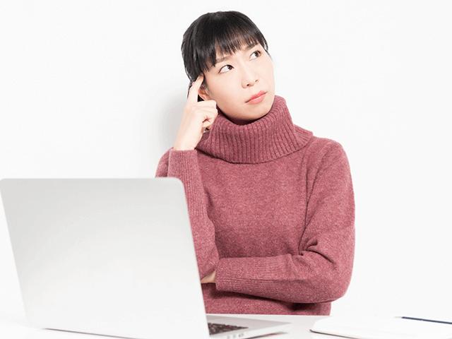ノートパソコンの前で悩む女性、PC