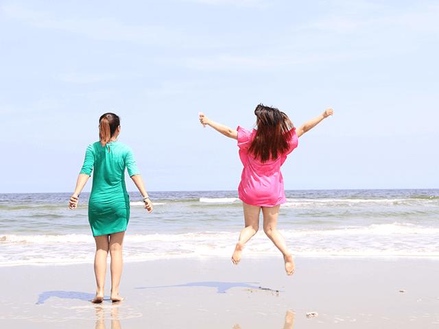 海・海岸・浜辺・波打ち際で万歳する女性