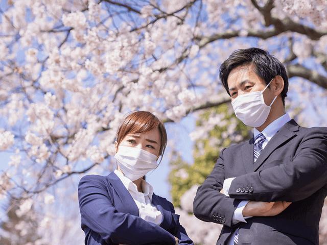 スーツの男女、マスク着用、悩む