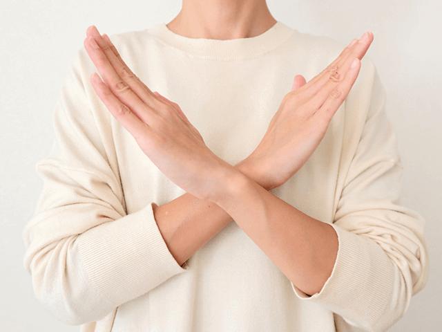 両腕を使って胸元でバツ印を作る女性