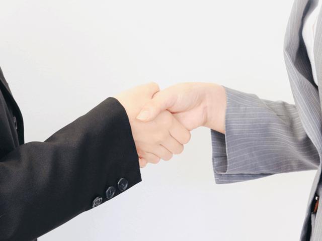 契約を結び握手をするスーツの2人
