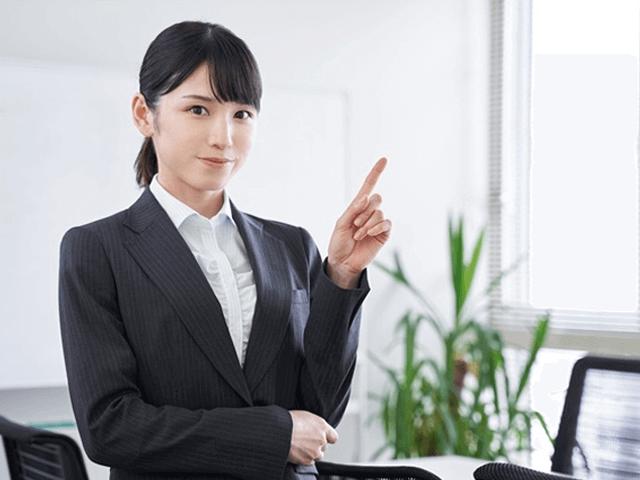 応接室で人差し指を立てるスーツの女性