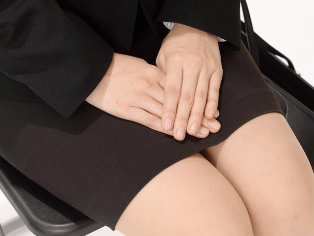 きちんと座るスーツの女性の手元