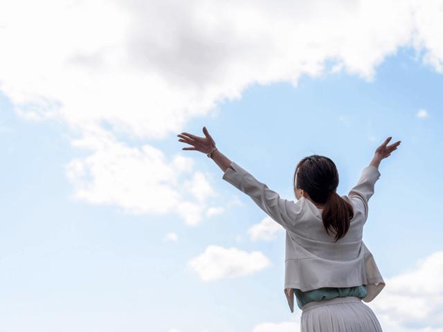 大空に向かって両手を上げるスーツの女性