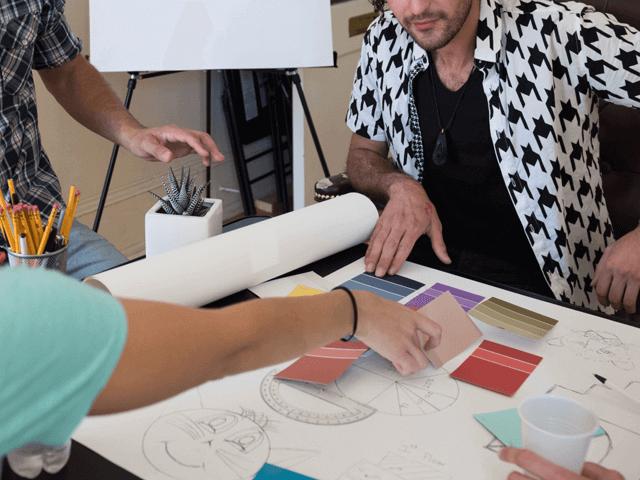 カラーチャートを出して会議するデザイナーたち
