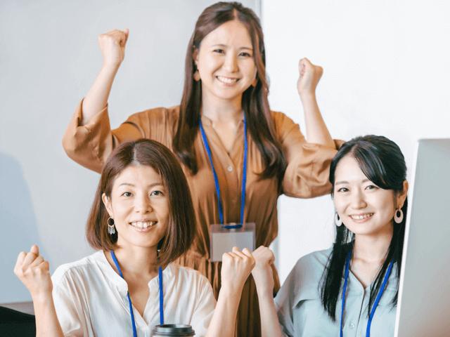オフィスでがっつポーズをする3人の女性