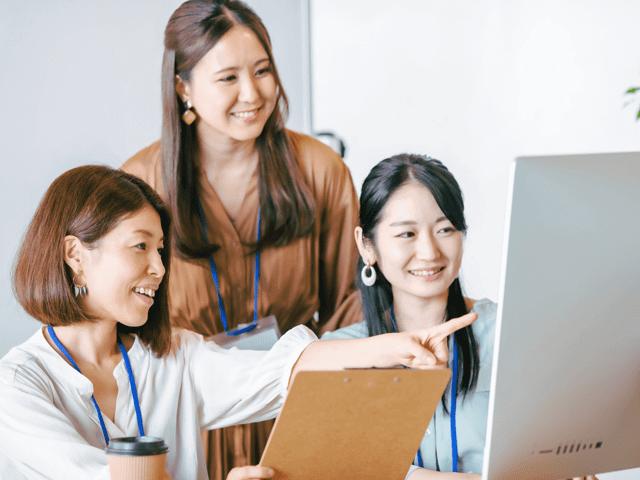 チームで作業をする笑顔の女性3人