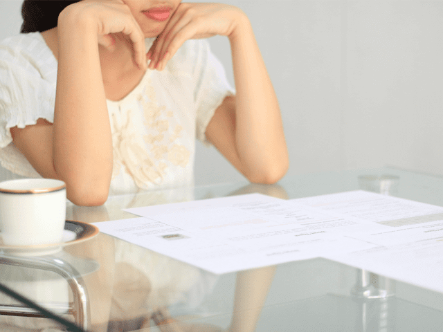 机上の書類を見ながら悩む女性