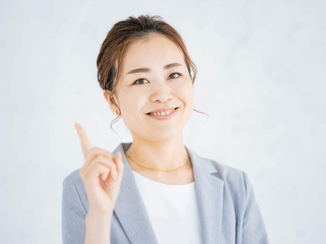 人差し指を立てる笑顔のスーツを着た女性